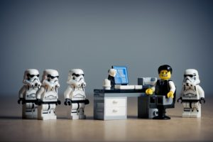 Lego office worker surrounded by droids. He is scared.